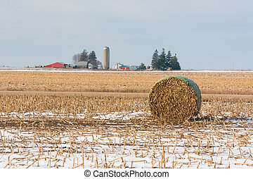 Bale of Hay in a Farmers Field with a Farm House in the Background