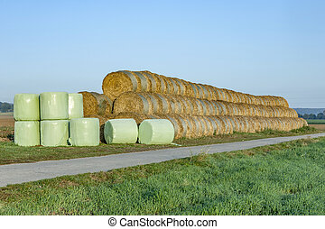 bale of straw at the field packed in platic foil