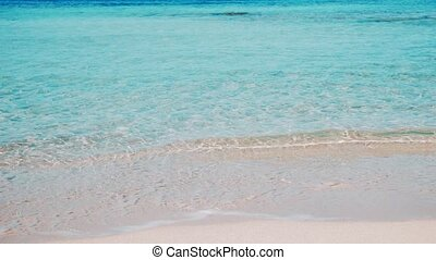 Spain Balearic island Ibiza Formentera , sunny summer day , calm transparent teal turquoise sea waves washing the shore of clean sandy paradise beach