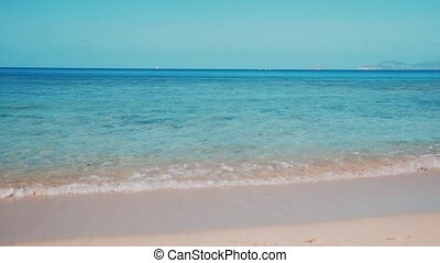 Spain Balearic island Ibiza Formentera , sunny summer day , blue sky , calm transparent teal turquoise sea waves washing the shore of clean sandy paradise beach