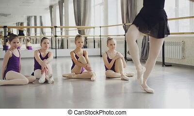 balerina, balet, jej, taniec, studenci, oglądając, mały, chodzi na palcach, tutor., podłoga, demonstrowanie, profesjonalny, posiedzenie, nauczyciel, ruchy