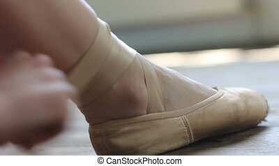 Balerina put on her pointe in the ballet hall