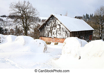 Bales of hay laying in the snow on