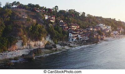Bali beach Dreamland with hotel on shore aerial view. Ocean rocky shore