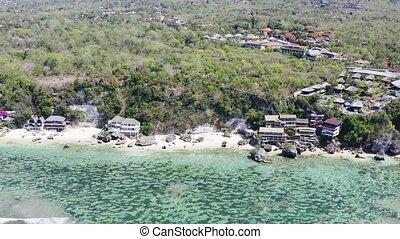 Bali beach with hotel resorts near Padang aerial view. Ocean rocky shore