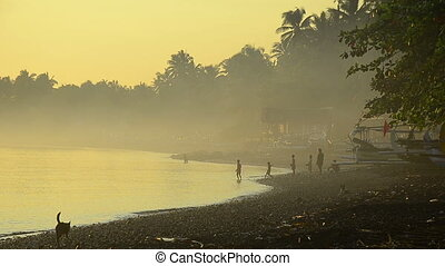 bali cost in morning fog with children fishing at the beach