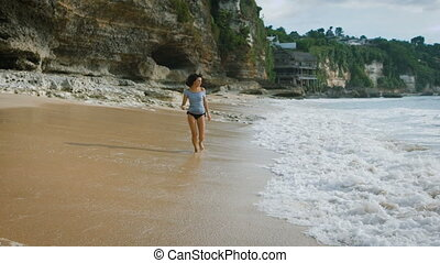Bali Island beach. Brunette smile runs across the sand on the beach and cool your feet in the water. Woman enjoying the sun, blue ocean. Against the backdrop of stunning views