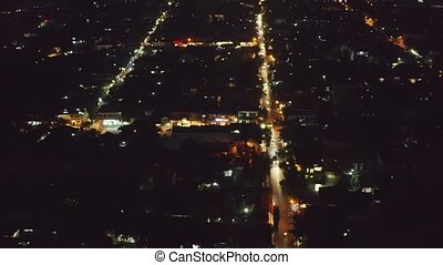 Night Ubud city aerial view to street with hotel and cafe on Bali, Indonesia