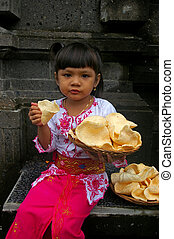 Balinese girl with a basket of Prawn Crackers