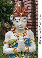 Balinese sculpture with red flower in garden in Lovina,...