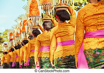 Balinese women carry ritual offerings on heads - Procession...