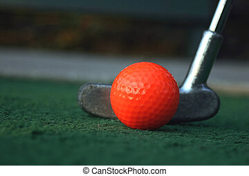 Close-up of a miniature golf ball and putter.