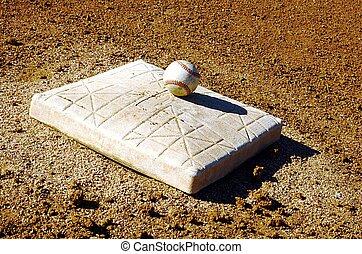 ball & base - Baseball sitting ontop of base in stadium.