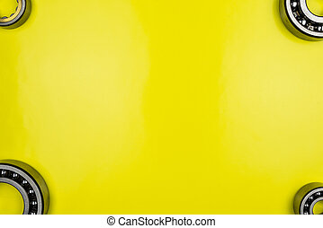 Ball bearing lying on a yellow background with copy space in the middle. Flat view from above.