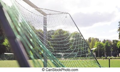 ball flying into football goal net on field - sport, soccer...