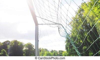ball flying into football goal net on field