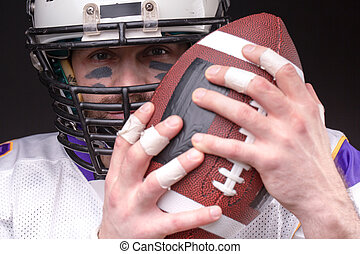 Ball for American football in front of footballer face