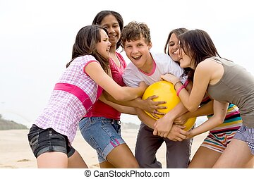 ball games - five teens having fun wrestling over a beach...