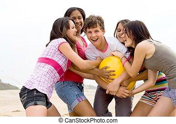 ball games - five teens having fun wrestling over a beach...
