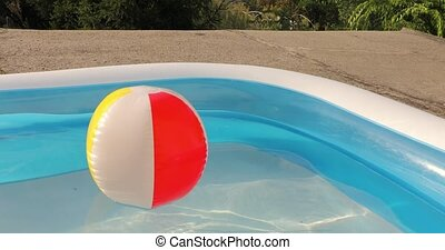 Ball in a garden inflatable pool in summer sunshine