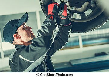 Ball Joint Vehicle Steering Maintenance by Professional Caucasian Car Mechanic. Automotive Industry.