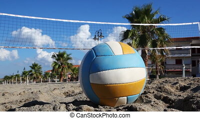 Ball lies on sand under volleyball net at beach