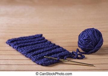 Ball of blue yarn with crochet needle