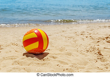 ball on sand near sea