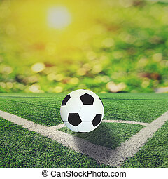 Ball on soccer field and orange bokeh and sun flare