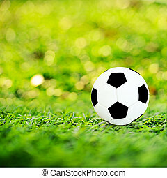Ball on soccer field with orange bokeh and sun flare