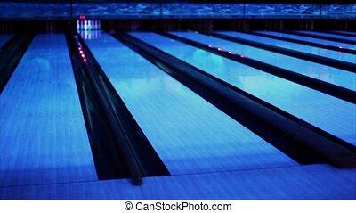 Ball thrundles in flume near bowling lane at dark club