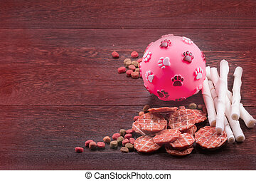 Ball toy for dog and dog snack ,dog Food, dog Chews, dog biscuits on a grey wooden table wall background with copy space .