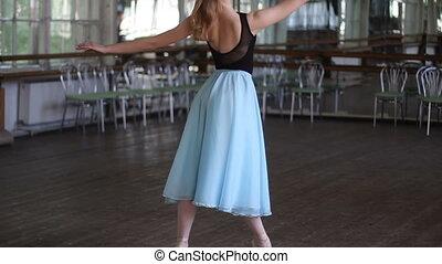 Ballerina dance on pointe in the ballet hall