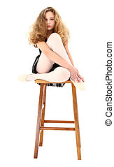 Ballerina girl child sitting on stool with clipping path over white.
