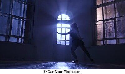 Ballerina girl practicing ballet in studio, moonlight silhouette. Slow motion