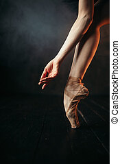 Ballerina hand and legs in pointes, black floor