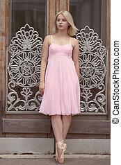 Ballerina in a pink dress posing