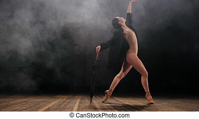Ballerina in black long jacket and sexy bodysuit dancing on...