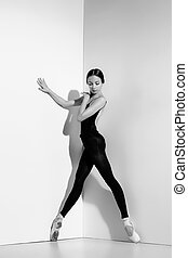 Ballerina in black outfit posing on pointe shoes, studio...
