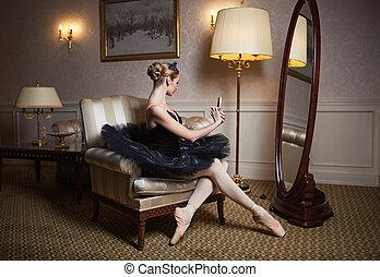 Ballerina in black tutu sitting in front of mirror -...