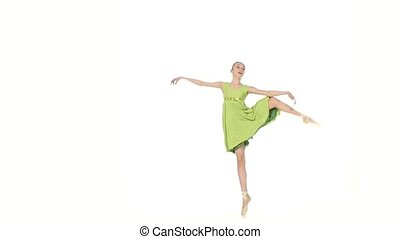 Ballerina in green dress posing on a white. slow motion