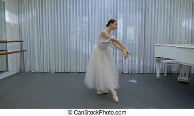 Ballerina in long ballet tutu dances in studio with white...