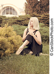Ballerina in pointe sitting on the grass