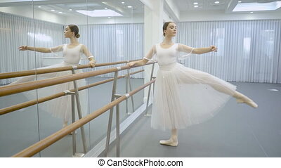 Ballerina in tutu and pointe is engaged near ballet machine....