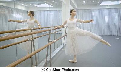Ballerina in tutu and pointe is engaged near ballet machine....