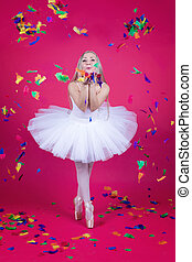 Ballerina in tutu skirt blowing feathers