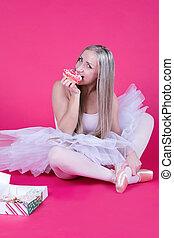 Ballerina in tutu skirt eating a donut