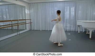 Ballerina in white ballet tutu and pointe shoes whirled in...