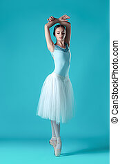 Ballerina in white dress posing on toes, studio background....