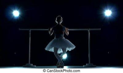 Ballerina in white tutu makes you lean forward. back view -...